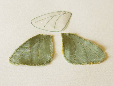 two underwings pictured with veins stitched and the paper pattern lying above them
