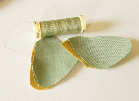 two cut pieces underwings in green satin, placed on two yellow cotton backing pieces