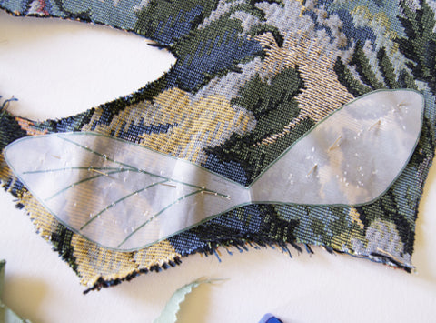 tracing paper wings pattern on tapestry close up of final placement