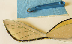 one sheet blue dressmakers tracing paper, a tracing wheel, the upper wings and the wing pattern