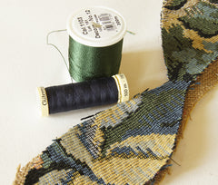 green thread and dark blue thread placed next to tapestry fabric for choice