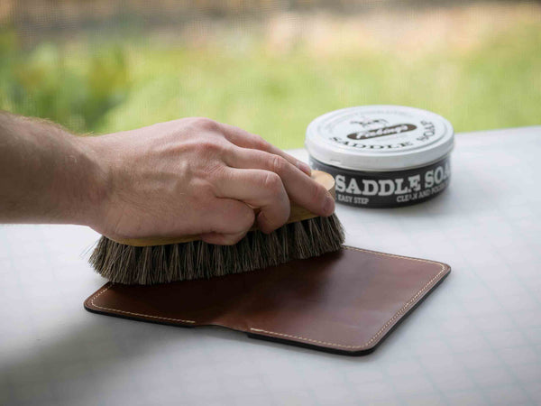 Buffing and cleaning leather goods with a horse hair brush from Saphir