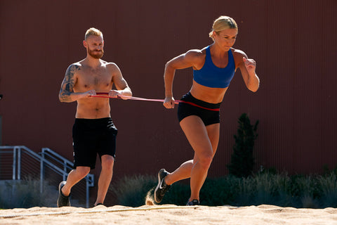 Male with blonde hair beard and tattoos works out with a large resistance band with a woman with blonde hair on the sand