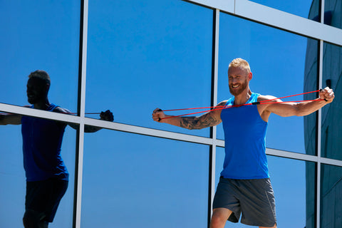 Blonde man with beard in blue sleeveless workout shirt who has tattoos works out with a red fitness band in front of large blue windows