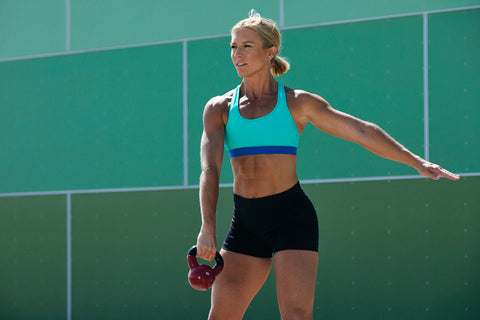 Blonde woman wearing a green and blue sports bra with black shorts swings a kettlebell in front of an ombre green wall