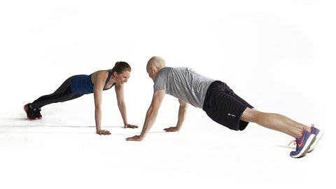 couple face each other in plank pose