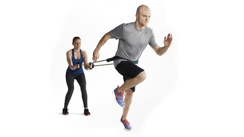 couple works out doing sprints with rubber resistance tubing