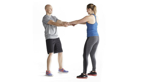 couple interlace hands preparing to squat facing each other