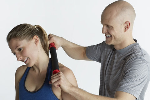 man uses tiger tail massager on womans neck