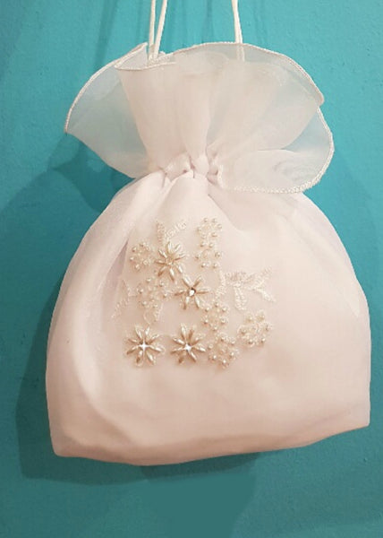 A lovely bag from the Little People Communion collection. Organza bag with delicate embroidery and scattered with flowered pearls and diamante. Two satin handles with a cluster of pearls adds to the finishing touch.