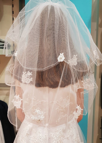 Truly stunning First Communion veil. A combination of woven flower motif and pearls embellish the tulle veil. Comb attached and ready to wear with or without a headpiece, and offers flexibility for different hair styles.