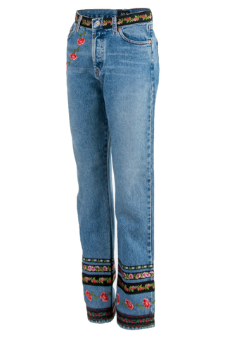 Side view of American made vintage classic blue high-rise straight leg jeans featuring patched floral print at leg opening and waist with patches at front and back pocket.