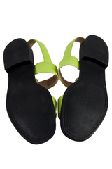 black soles of green strappy sandals