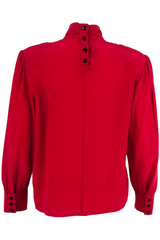 red blouse with black buttons at neck
