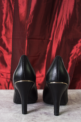black leather pumps with gold trim