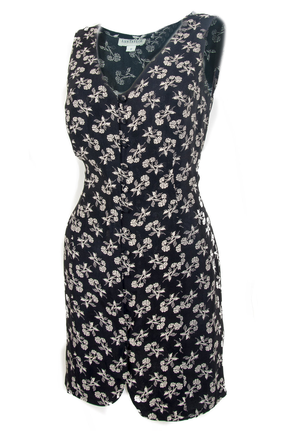 Side view of vintage sleeveless tunic with all-over floral print tie strings at back and front button closure.