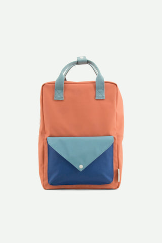 A rusty red, ink blue & denim blue large backpack with a fun envelope pocket from Sticky Lemon