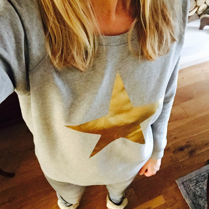 Metallic gold star on a light grey sweatshirt