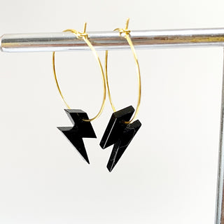 Little black lightning strikes on a gold hoop earring