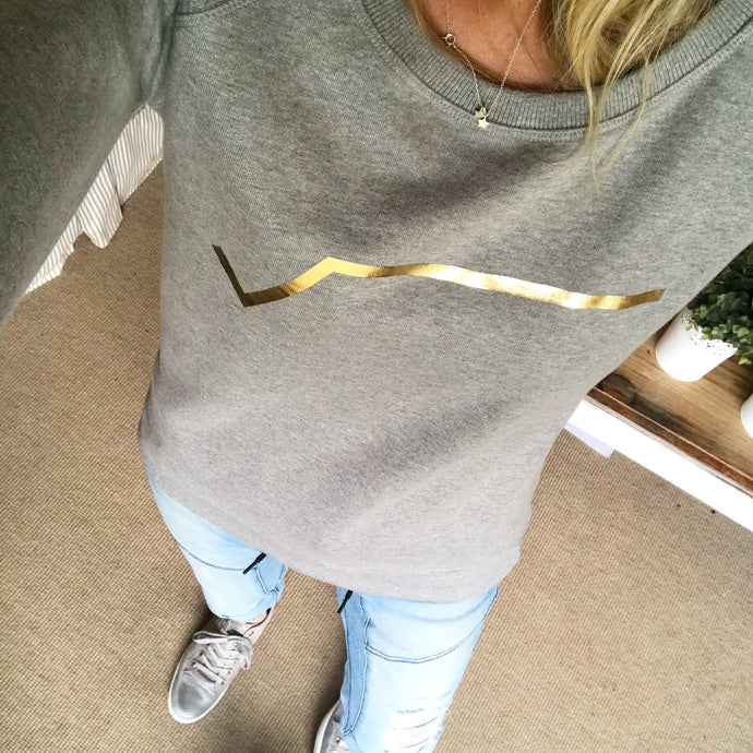 Gold diagonal stripe on light grey sweatshirt