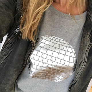 Silver disco ball on a light great sweat