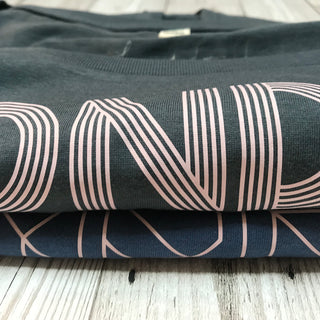Pink geometric aurora font on denim blue tee