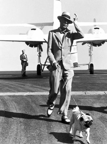 king Edward VIII walking his pug away from a plane dressed in two-tone shoes.