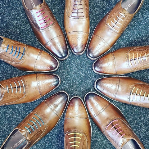 A birds eye view of ten Arthur Oxford Shoes in Chestnut from London brogue placed in a circle with the toes facing inwards, each with a different coloured lace