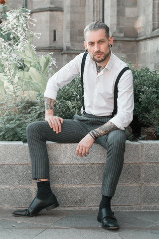 Man sat on wall in suit trousers and suspenders over a white shirt. He is wearing black oxfords and his black socks have risen up.