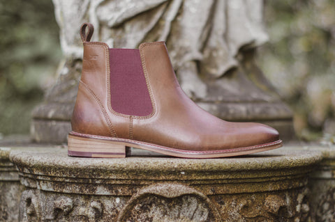 A brown Chelsea boot with burgundy elastic panel, stood on a stone plinth in a graveyard.
