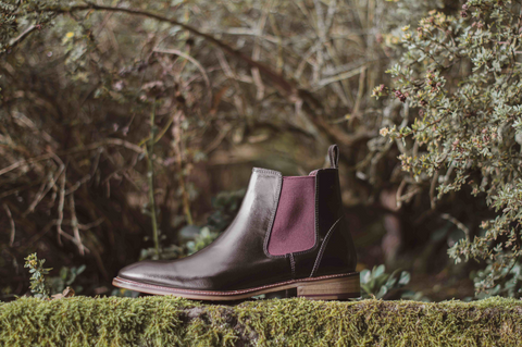 London Brogues hamilton chelsea boot in black leather with bordo elastic side panel on top of a hedge.