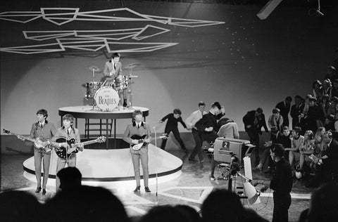 Black and white photograph of the beatles performing on a stage wearing their 1960s 'uniforms' showing their chelsea boots with cuban heels