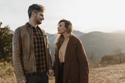 A white man with salt and pepper hair in his late thirties dressed in a brown leather jacket with a brown and grey check shirt looking over to a pretty blonde white woman in a rust coloured wool coat and soft brown sweater. They are stood in front of a vista of mountainous terrain with shrubby and heath like plants.