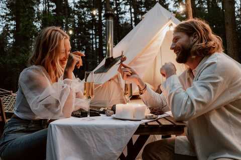 couple glamping in woods and eating a candle lit meal together