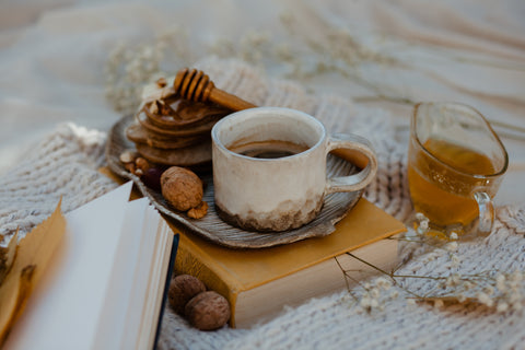 A rustic still life set up of a cup of tea in a rustic pottery cup and saucer placed on an old hardback book. Surrounding it are dried flowers, nuts, a honey drizzler and glass jug of honey. These are all placed on top of a white knitted blanket