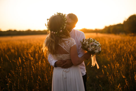 A bridal couple stood kissing in a cornfield with the sunsetting behind them.