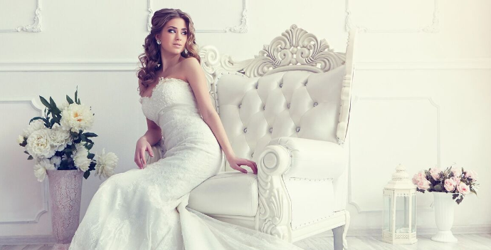 Woman in wedding dress sitting on chair