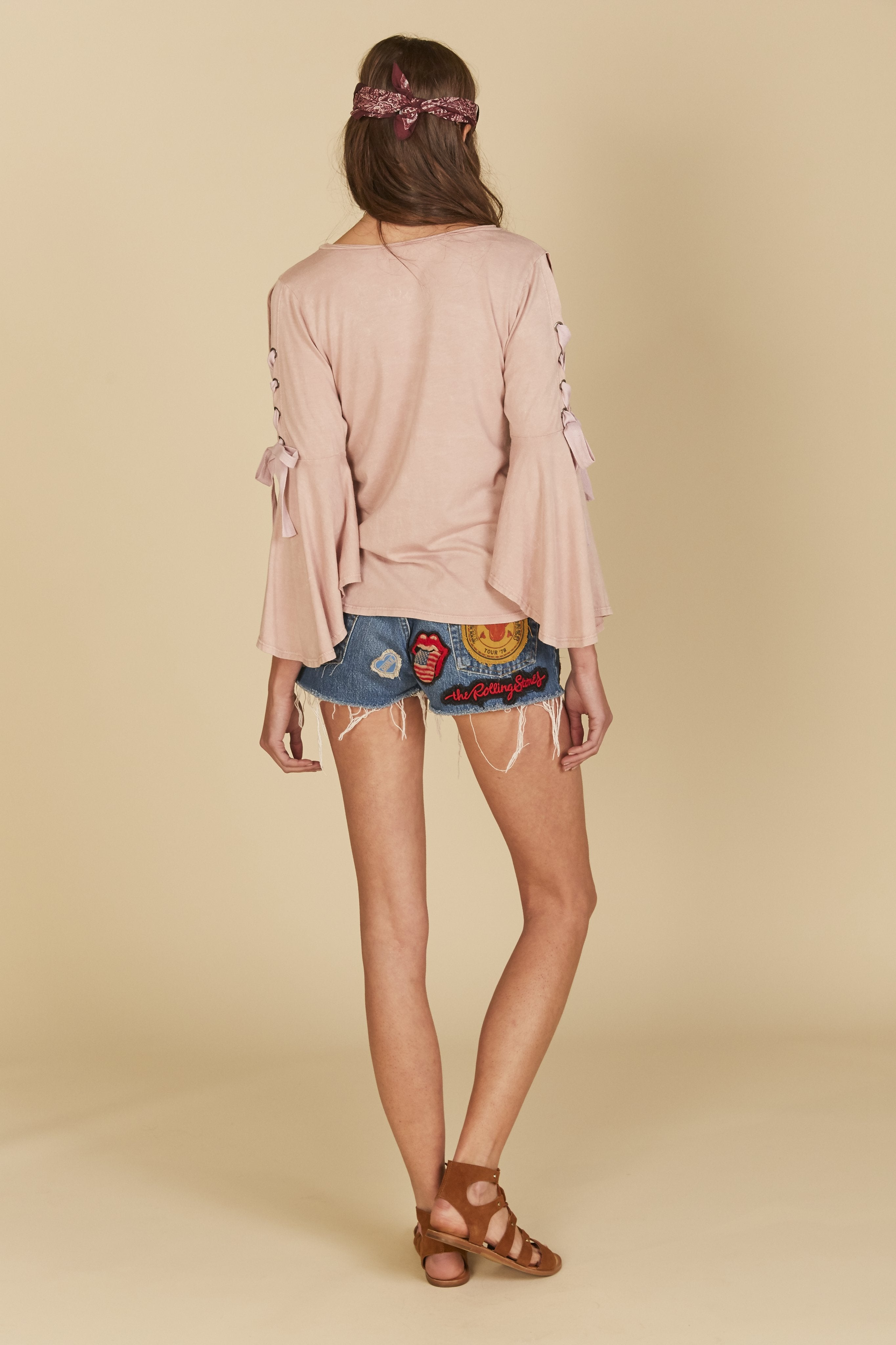 Solid scoop neck pink mauve top featuring lace up bell sleeves with grommets.