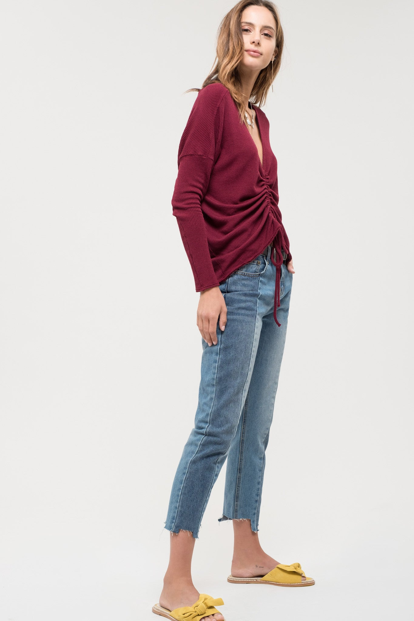 Solid long sleeve burgundy knit top featuring ruching detail with self tie.