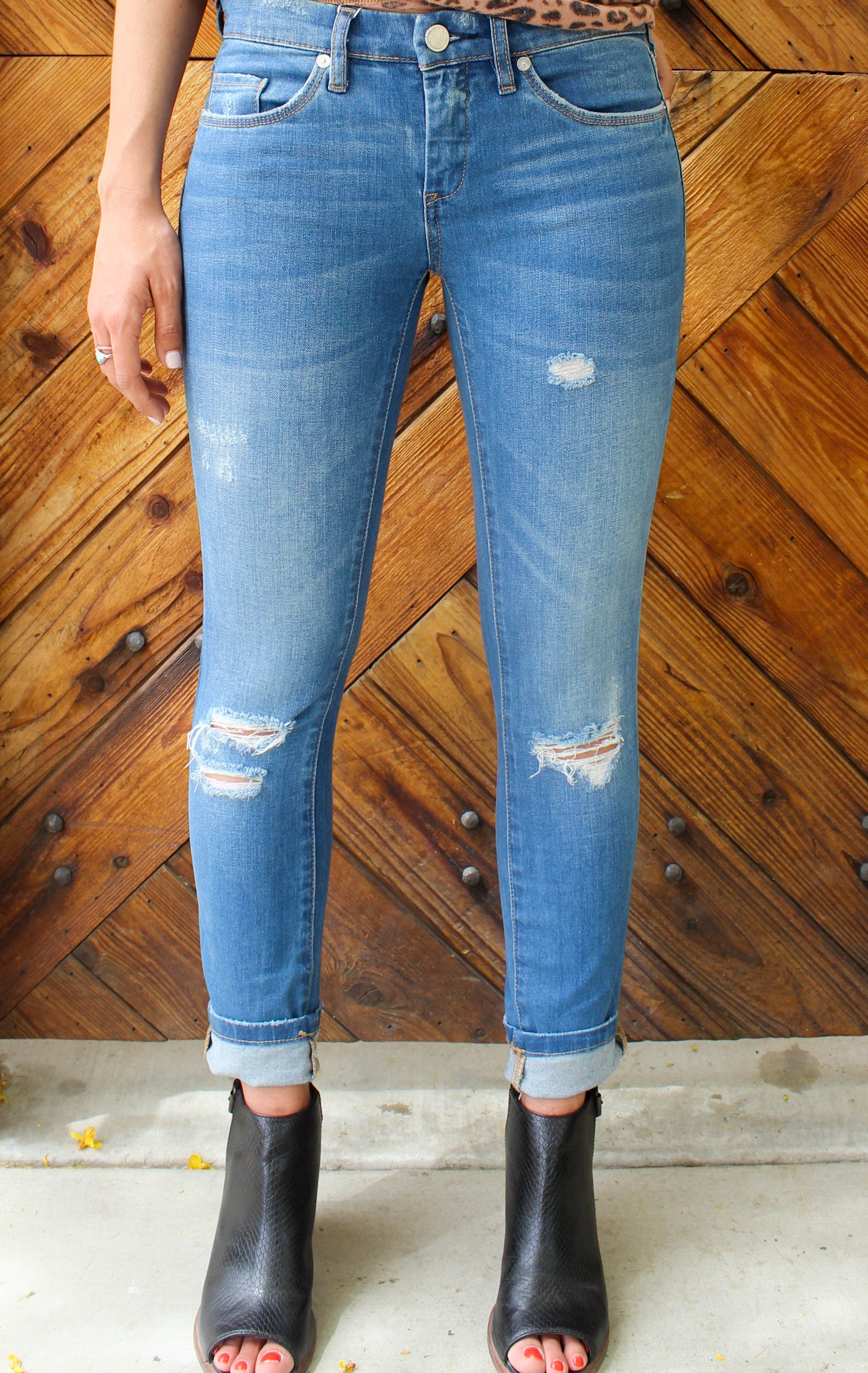 Blue denim ankle skinny jeans distressed along the knees.