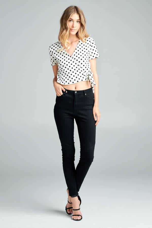White short sleeve surplice crop top with black polka dots and a front tie detail.