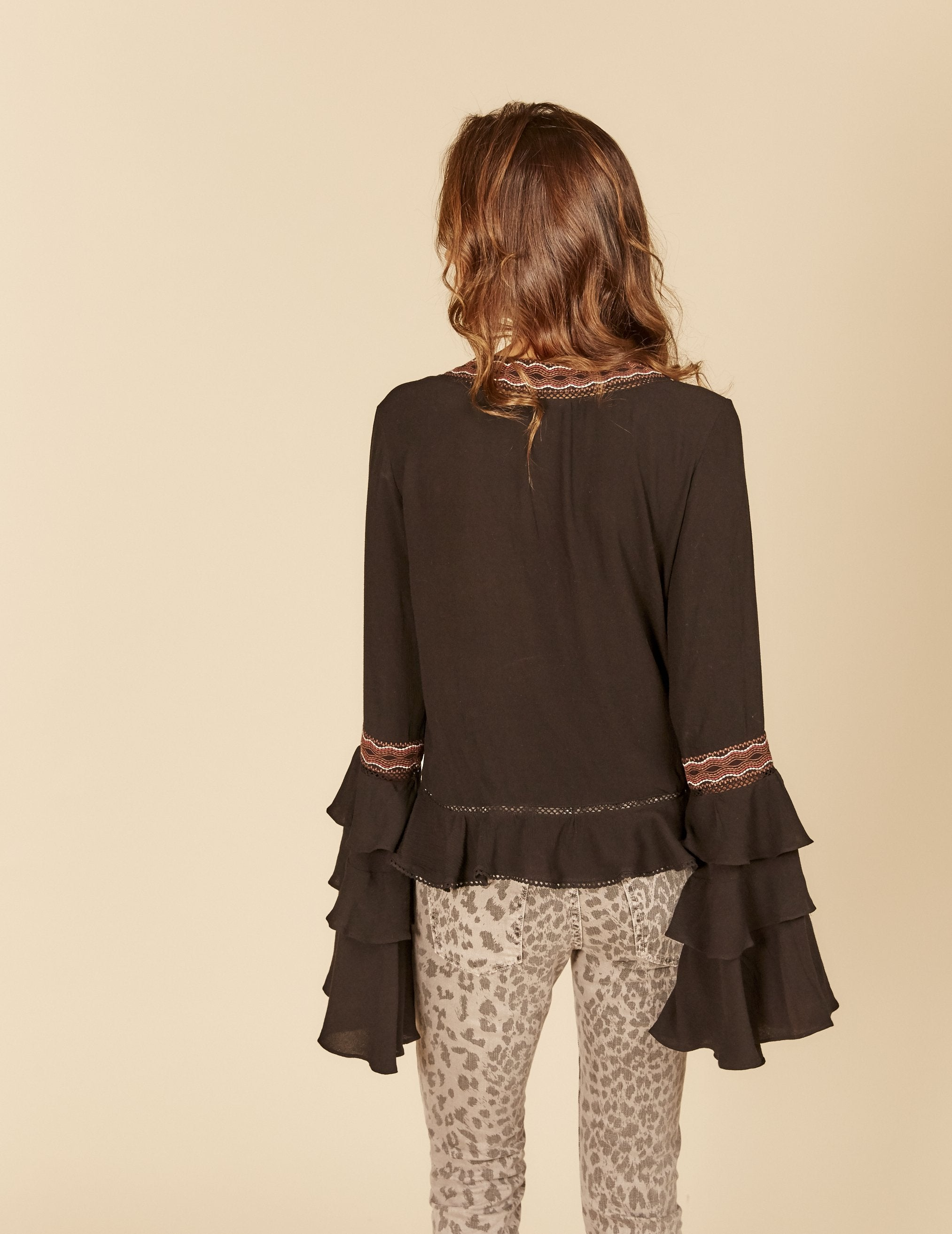 The Black Embroidered Blouse features a v-neck, 3 tier ruffled bel sleeves and an embroidered trim front tie detail.