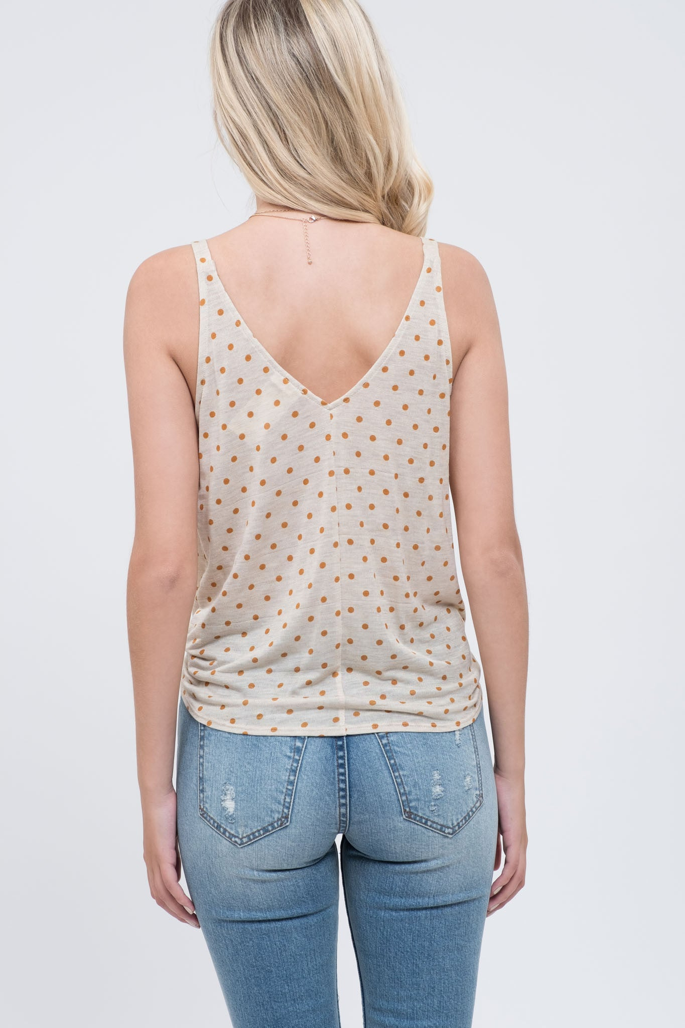 Ivory tank top with orange polka dots featuring a front tie detail.