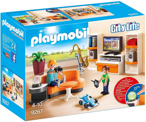 "A blue Playmobil box with a picture of a living room. In the room are two light skinned figures, a man and a boy. The man is holding a camera, the boy is holding the remote to a car near him. There is a couch, a light on a stand, a plant, a saxophone in a stand, and a bookcase with a TV and books on it. The text on the box says: City Life, Playmobil 9267, 4-10, and a diagram of how to turn on the table lamp by pushing a button with text that says ""with colour-changing LED""."