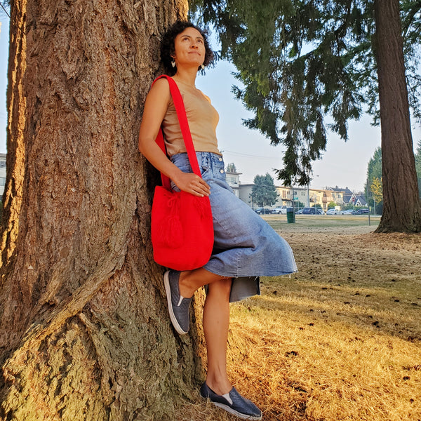 Valentina Pinzon, owner of Indiarts Collective weating a beautiful red mochila bag and tringle beaded earrings. Chilling at a park in Vancouver.