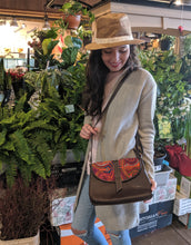 Woman looking down at her medium crossbody bag with mola design over her shoulder.