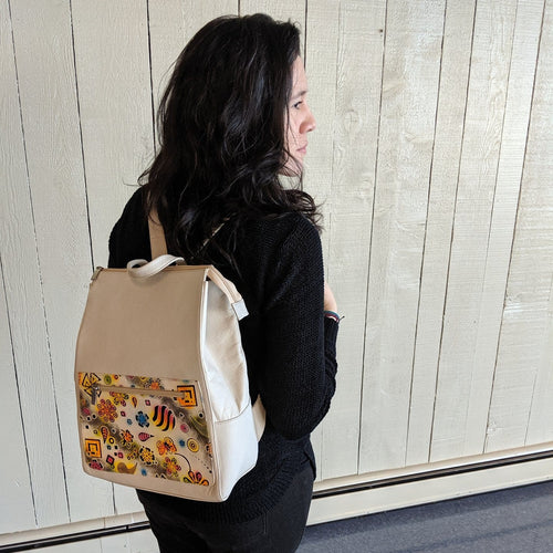 Woman with dark hair and a white backpack with hand painted and hand stamped decoration