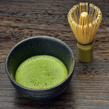 organic matcha green tea powder mixed in bowl with bamboo whisk