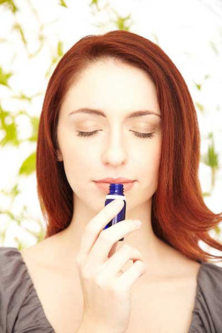 Aromatic sense of smell - woman sniffing lavender essential oil from an essential oil bottle