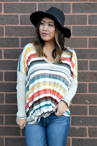 Grab this top now or you'll regret it Down The Line! The soft top features trendy multi-colored stripes on the bodice and drop shoulders, solid waffle knit sleeves and relaxed fit with flattering twist front.
